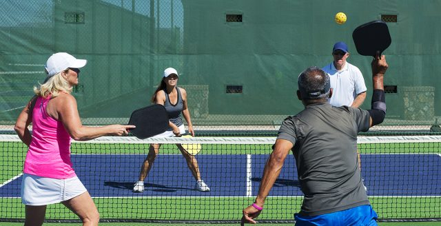 colorful action image of two couples playing a game of pickleball